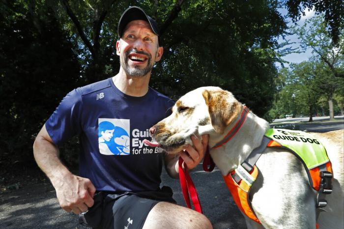 Thomas Panek pauses with his Labrador retriever, Blaze, a trained guide dog, after running in Central Park.