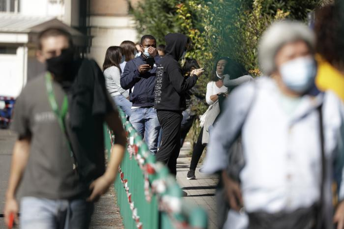 People wait in line outside San Giovanni hospital to get tested for COVID-19, in Rome on Oct. 8, 2020.