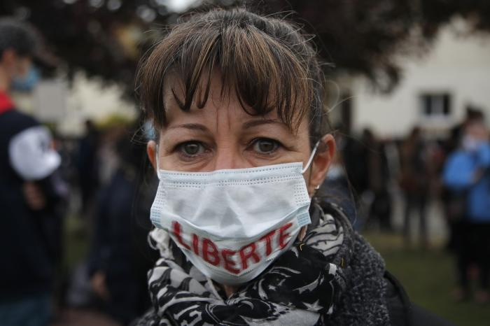 """A woman wears a mask reading """"Freedom"""" as residents gather outside the school where a slain history teacher was working, Saturday, Oct. 17, 2020 in Conflans-Sainte-Honorine, northwest of Paris"""