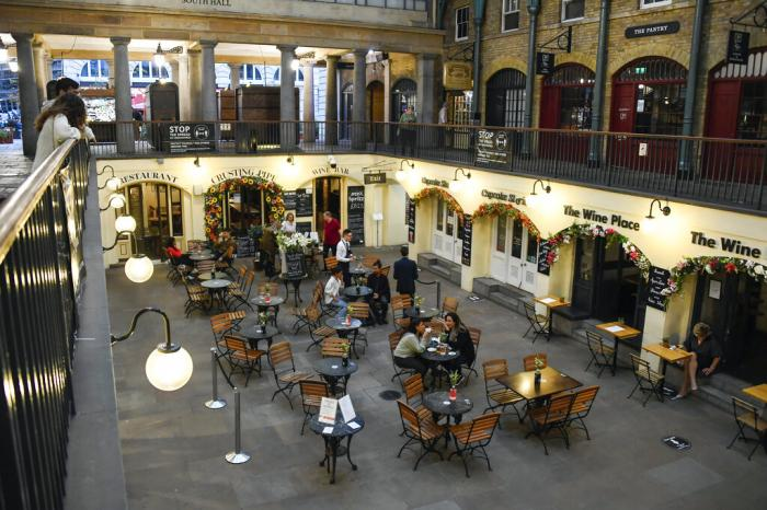 People are seated eating and drinking in Covent Garden, in London.