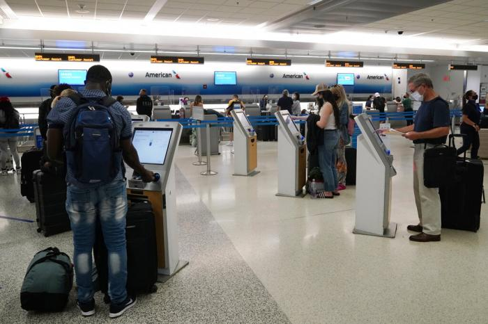 Travelers use the self-service kiosk to check in and pay for luggage at the American Airlines terminal in Miami.